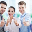Coworkers showing thumbs up — Stockfoto