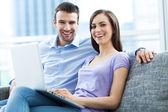 Couple on sofa with laptop — Stock Photo