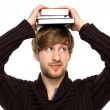 Man balancing books on his head — Stockfoto