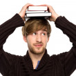 Man balancing books on his head — Stock Photo