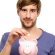 Man putting coin in piggy bank — Stock Photo