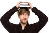 Man balancing books on his head — Stock Photo