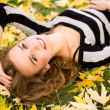Womlying down in autumn leaves — Foto de stock #27704707