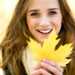 Stock Photo: Woman holding autumn leaf