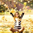 Girl throwing autumn leaves in air — Stock Photo