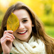 Woman holding autumn leaf — Stock Photo