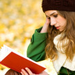 Stock Photo: Girl reading book outdoors