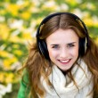 Girl listening music outdoors — Stock Photo #27705755