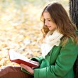 Girl reading book outdoors — Stock Photo