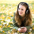 Girl listening music outdoors — Stock Photo #27706905