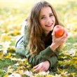 Woman eating apple outdoors in autumn — Stock Photo