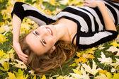 Donna sdraiata in foglie di autunno — Foto Stock