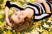 Woman lying down in autumn leaves — Stok fotoğraf