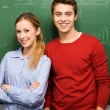 Students standing next to blackboard — Stock Photo