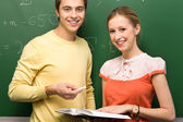 Students by chalkboard — Stock Photo