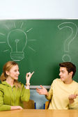 Two students with light bulb and question mark on chalkboard — Stock Photo