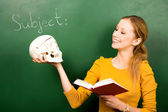 Female student holding skull and book — Stock Photo