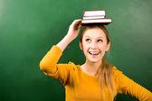 Female student balancing books on head — Stock Photo