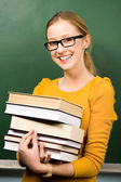 Female student at chalkboard with books — Stock Photo