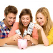 Young putting money in piggy bank — Stock Photo