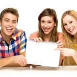 Grupa przyjaciół, trzymając papier blank — Zdjęcie stockowe