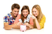 Young putting money in piggy bank — Foto de Stock