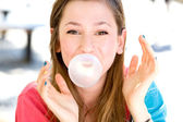 Mladá dívka foukání žvýkačky — Stock fotografie