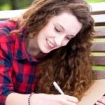 Girl doing her homework outdoors — Stock Photo #27868415