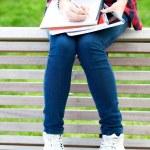 Girl doing her homework outdoors — Stock Photo #27868431