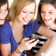 Stock Photo: Three Female Friends Laughing and Looking at Cell Phone