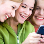 tres amigas riendo y mirando el teléfono celular — Foto de Stock