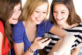 Three Female Friends Laughing and Looking at Cell Phone — Stock Photo