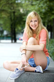 Young woman sitting outdoors — Stock Photo