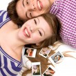 Young couple lying down with photos — Stock Photo