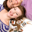 Young couple lying down with photos — Stock Photo #27882547