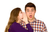 Woman whispering into man's ear — Stock Photo