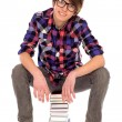 Stock Photo: Young man sitting on pile of books