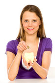 Woman putting coin in piggy bank — Stock Photo