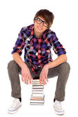 Young man sitting on pile of books — Foto Stock