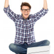 Man with arms raised using laptop — Stock Photo #27950057