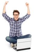 Man with arms raised using laptop — Stock Photo