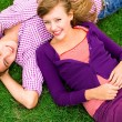 Couple lying down on grass — Stockfoto