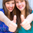 Young women giving thumbs up — Stock Photo #28042885
