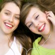 Two teenage girls listening to MP3 player — Stockfoto