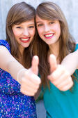 Young women giving thumbs up — Stock Photo