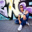 Young man sitting against graffiti wall — Stock Photo #28056061