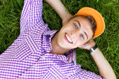 Young man lying down on grass — Stock Photo