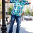 Young man hanging on lamp post — Stock Photo