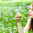 Gorgeous young girl blowing soap bubbles in park. — Stock Photo