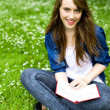Young woman sitting with book on grass — Stock Photo